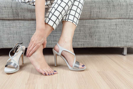 leg massage: woman sit on chair and female hand with foot pain after, take shoes off Stock Photo