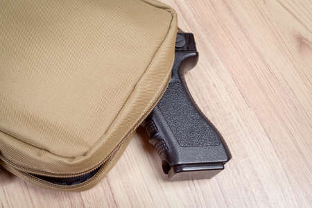 concealed: weapon gun in bag, khaki or sand color, on table background