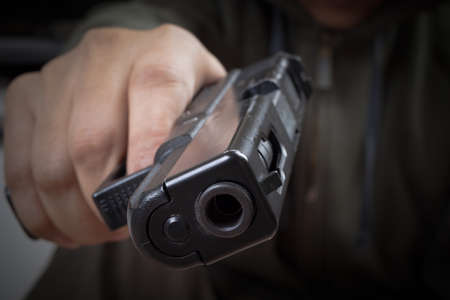finger on trigger: gun in hand and pointing with killer, safety and criminal concept background