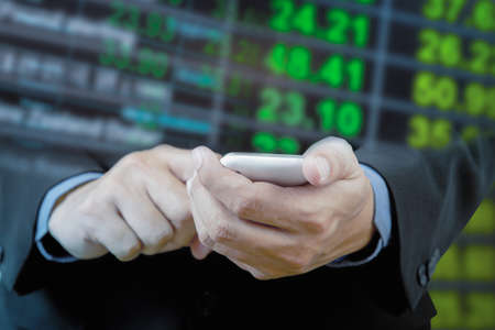 exchange rate: Businessman touch smart phone in hand with exchange rate blur background Stock Photo