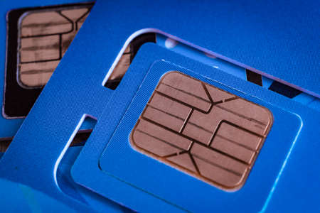 sim card used of mobile smart phone close up macro shot on blue card background, technology concept theme