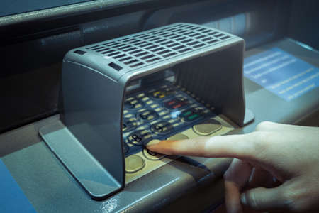 numpad: finger point at A.T.M. numpad keypad with guard for protect and use deposit or withdraw money, closeup Stock Photo
