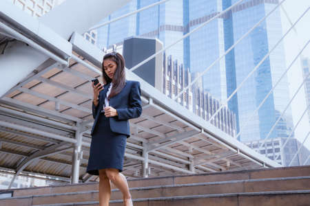 asian business woman standing and use smartphone with business building background