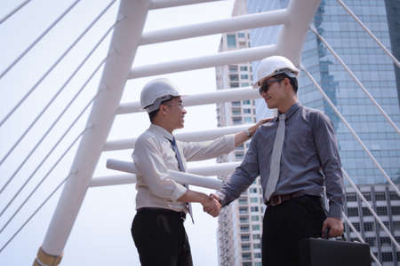 suite: Asian businessman discuss and shake hand with engineer architect professional wearing safety helmet and suite, holding construction roll plan and briefcase for working team concept Stock Photo