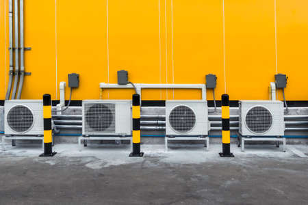 air conditioner compressor installed outside building with yellow and black warning pole on the ground