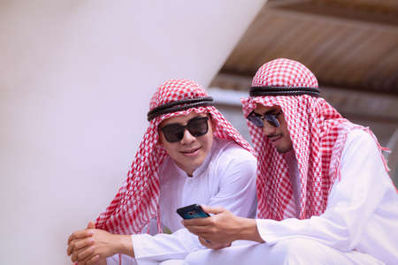 Arabian businessman using cell phone with colleauge for presenting business concept background Standard-Bild