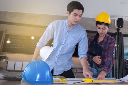 professional male and female engineers working and discuss with blueprint business together