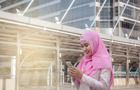Arabian business woman smiling happy to use cell phone and modern business city background