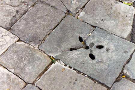 pothole: A pothole in a road. Broken stone pavement dangerous to motorists
