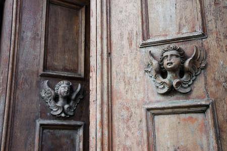 angel statue: Sculpture of an angel on a wooden door in Italy