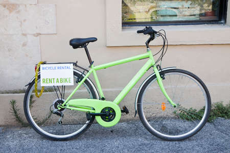 Green bicycle for rent against the wall photo
