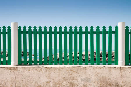 delimitation: Green fence in front of the sea Stock Photo