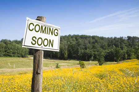short phrase: Coming Soon concept - Coming Soon concept written on a field sign Stock Photo