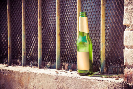 mental health problems: Bottle of beer left on the windowsill of an old window: alcoholism concept