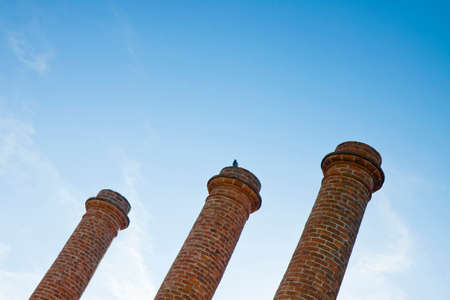 Three old brick chimney isolated on sky with copy space photo