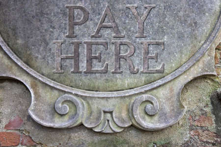 pay wall: Pay Here concept - Pay Here written on a stucco wall