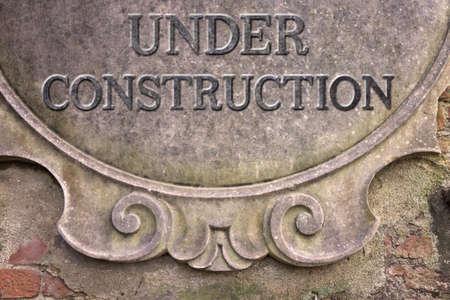 short phrase: Under Construction concept - Under Construction written on a stucco wall
