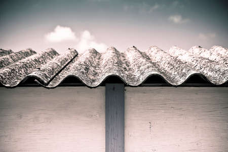 Dangerous asbestos roof - Medical studies have shown that the asbestos particles can cause cancer -toned image photo