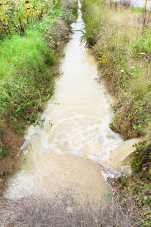 Ditch in a field after torrential rain photo