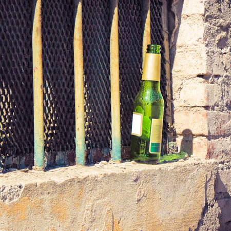 single beer bottle: Bottle of beer left on the windowsill of an old window: alcoholism concept
