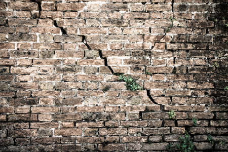 infiltration: Cracked brick wall - Deep crack in a brick wall - toned image Stock Photo