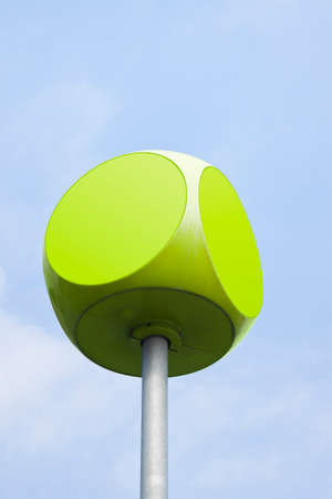 insertion: Green cube with rounded edges against sky background with copy space
