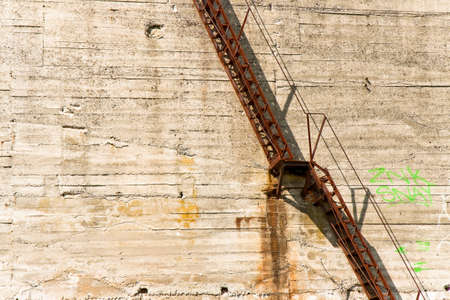 come up to: Old iron staircase against a concrete wall Stock Photo