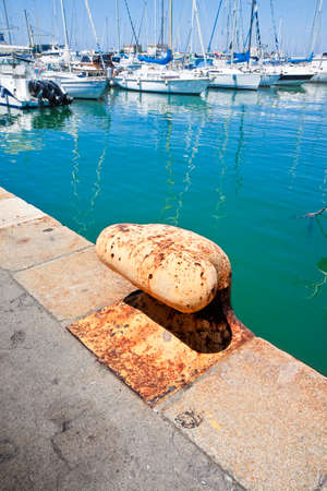 landfall: Yellow cleat for mooring boats. Old bollard in a italian harbour Stock Photo