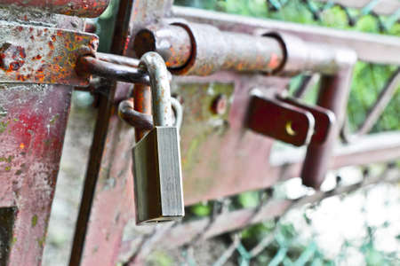 metal gate: Red metal gate closed with padlock - concept image Stock Photo