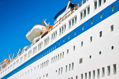 lifeboats: Large cruise ship with lifeboats on blue background