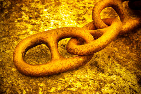 rusty chain: Detail of an old rusty metal chain anchored to a concrete block - toned image