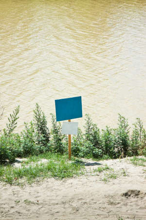 insertion: Colored blank signboard by the river - With space for text insertion. Stock Photo