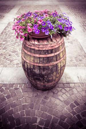 toned image: Wooden barrel with flowerpot above - toned image Stock Photo