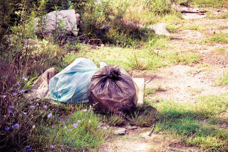 criminal activity: Illegal dumping in the nature; garbage bags left in the nature - toned image Stock Photo