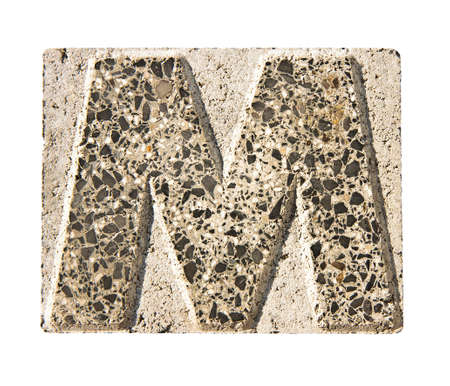 concrete block: Letter M carved in a concrete block - A concrete block with the letter M carved into it.