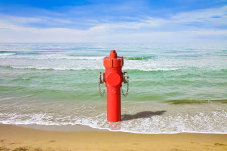 A hydrant at the seaside. Plenty of water: concept image