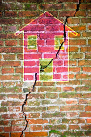 cracked wall: Cracked brick wall with a colored house drawn on it Stock Photo