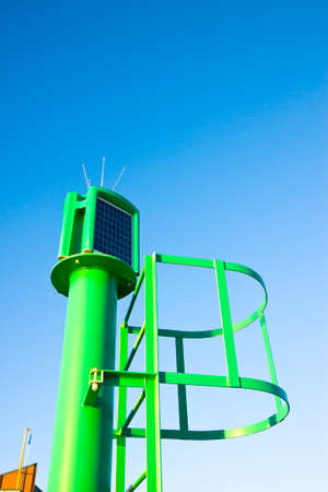 nautical structure: Colorful little lighthouse with staircase against a blue sky