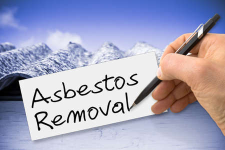removing the risk: Hand writing Asbestos removal with a pencil on a blank sheet