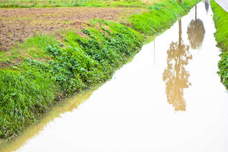 alluvial: Full water ditch in a field after torrential rain -  Image with copy space Stock Photo