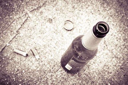 abuso: Botella de cerveza en reposo en el suelo con las culatas de tres de cigarrillos. El alcoholismo y la adicci�n al tabaco concepto - imagen de tonos