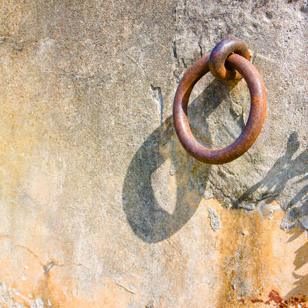 medieval blacksmith: Old iron ring fixed in a plaster wall - toned image