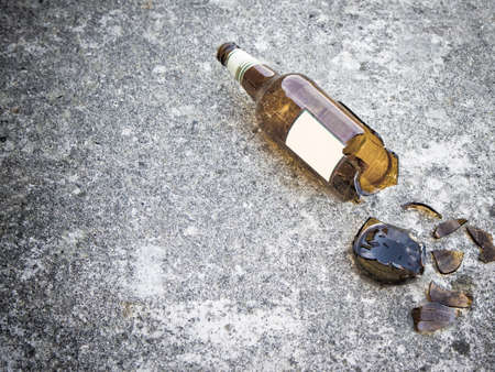 Shattered brown beer bottle resting on the ground: alcoholism concept - toned image