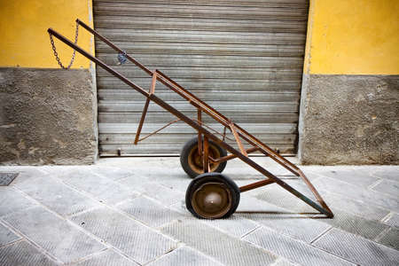 pushcart: Old metal pushcart against a colored wall Stock Photo