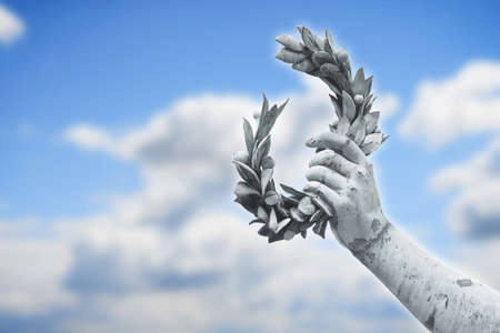 hand held: Laurel Wreath hand held by a bronze statue on sky background whit copy space Stock Photo