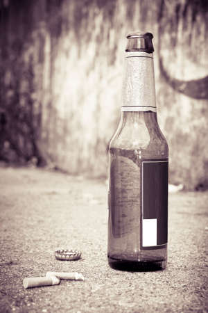 fag: Bottle of beer resting on the ground with three cigarettes butts. Alcoholism and tobacco addiction concept - toned image