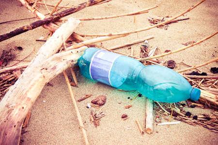 basura: Botella vacía de plástico verde abandonada en la playa