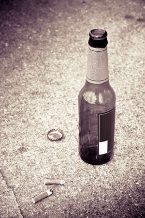 single beer bottle: Bottle of beer resting on the ground with three cigarettes butts. Toned image
