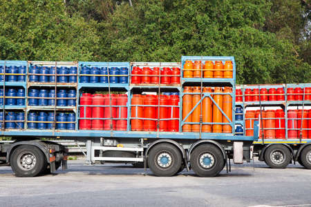 propane: Trucks parked on a street load of colored propane gas tanks Stock Photo