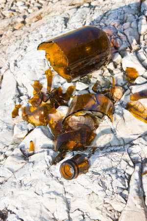 smithereens: Shattered beer bottle resting on the ground: alcoholism concept